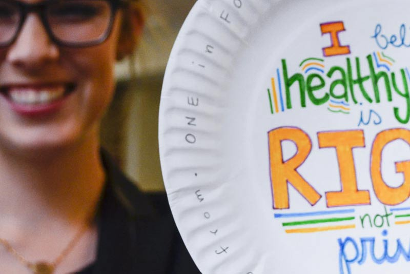 Photo of smiling female college student holding a paper plate with a handwritten message